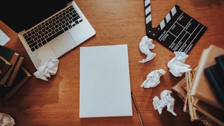 Vista dall'alto delle cose di Text Writer sul posto di lavoro. Primo piano del desktop in legno con laptop, fogli di carta stropicciata, pile di libri e ciak film. Concetto di giornalismo e sceneggiatore