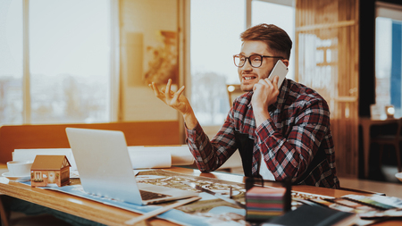Guy Working on Project Has Phone Conversation. Portrait of Young Bearded Hipster Illustrator Sits at Workplace Using Laptop and Smartphone . Creative Graphic Designer Job Concept