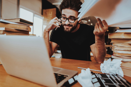 Artist Text Writer With Movie Clapper Sits Indoor. Portrait of Handsome Journalist or Screenwriter Sitting at Desk With Two Big Pile of Books Using Laptop Holds White Papers and Talking on Phone