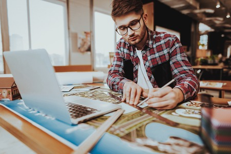 Portrait of Young Graphic Designer Works Indoors. Bearded Illustrator Wearing Glasses Sitting at Workplace Doing Design Project Using Pencil and Ruler Looking at Palette. Creative Job Concept