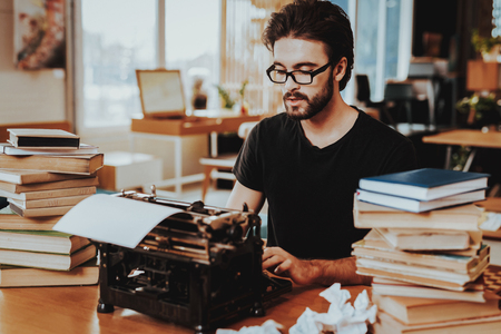 Concept of Young Guy Working on Typewriter. Handsome Hardworking Freelance Screenwriter Scenarist Sitting at Table Near Stacks of Books and Crumpled Paper Sheets Writing Article, Novel, Play. Imagens - 127394267