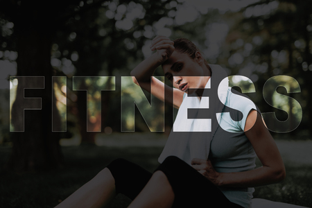 Woman Wiping Sweat from Forehead. Girl Rest after Workout. Woman Sit on Rug for Yoga. Young Fitness Woman. Girl in Fitness Training. Female Do Exercises in Park. Persone Leads Healthy Lifestyle. Banco de Imagens