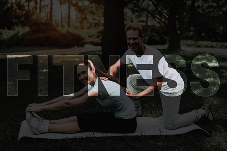 Young Fitness Woman. Man Helping Girl Stretch. Girl Doing Stretching on Rug. Yoga in Park. Girl in Fitness Training. Female Do Exercises in Park. Person Leads Healthy Lifestyle. Woman Smiles.