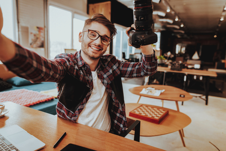 Smiling Guy Make Selfie when Working at Workplace. Portrait of Stylish Bearded Smiling Handsome Caucasian Photographer Wearing Glasses Holds Professional Camera in Hand Sits at Table Indoors.