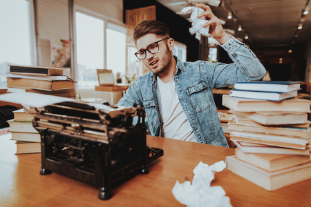 Nervous Sad Freelancer Working on Vintage Typewriter. Portrait of Disappointed Upset Textwriter, Screenwriter or Scenarist Throwing Crumpled Paper Sheets Sitting at Desk. Retro Style of Work. Imagens