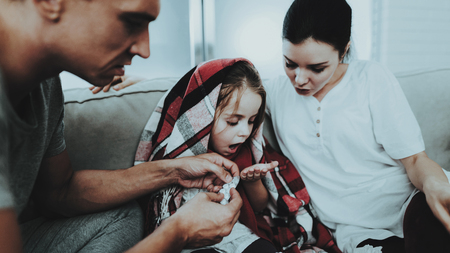 Little Girl in Red Scarf with Cold with Family. Sick Young Girl. White Sofa in Room. Father and Mother. Disease Concept. Healthcare and Healthy Lifestyle Concept. Take Care of Daughter.
