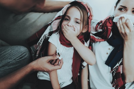 Sick Family Sitting on Sofa in Checkered Blankets. Mother and Daughter. White Sofa in Room. Unhappy Girl. Disease Concept. Healthcare and Healthy Lifestyle Concept. Using Serviettes. Father with Family.