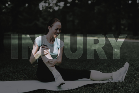 Woman Sit on Rug for Yoga. Girl Clings Injured Leg. Female Hurt Leg. Girl Stretching on Rug. Yoga in Park. Young Fitness Woman. Girl in Fitness Training. Person Leads Healthy Lifestyle. 写真素材