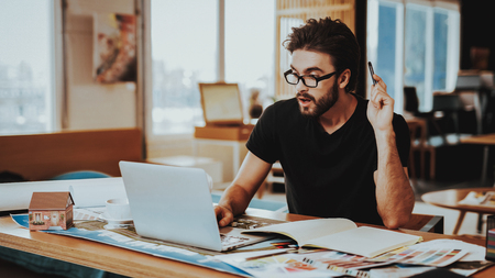 Portrait of Guy Sitting at Desk Works at Project. Young Bearded Graphic Designer Illustrator Wearing Glasses Sitting at Table Focused at Laptop Screen . Creative Job Concept Stock Photo