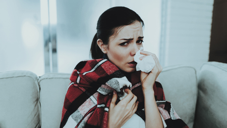 Woman with Cold on Sofa in Checkered Blanket. Girl at Home. Sick Young Woman. White Sofa in Room. Unhappy Woman. Disease Concept. Healthcare and Healthy Lifestyle Concept. Using Napkins.