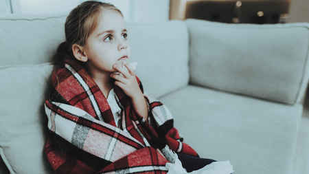 Little Girl with Cold Sitting on Sofa in Blanket. Sick Young Girl. White Sofa in Room. Unhappy Child. Disease Concept. Healthcare and Healthy Lifestyle Concept. Little Girl at Home.