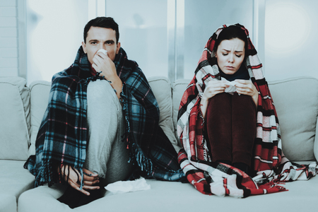 Sick Couple Sitting on Sofa in Checkered Blankets. Man at Home. Sick Young Woman. White Sofa in Room. Unhappy Guy. Disease Concept. Healthcare and Healthy Lifestyle Concept. Using Napkins.