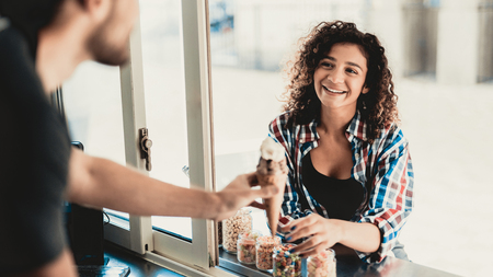 Woman in Shirt Buying Ice Cream in Food Truck. Promenade in Town. Summer Day. Girl in Checkered Shirt. Street Food Concept. Cup of Coffee. Buying Food Outdoor. Food in Town. Selling Snacks.