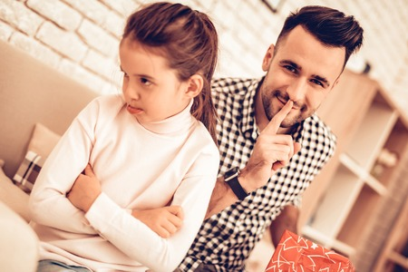 Video Game in Hand. Virtual Reality Mask. Father and Daughter on Sofa. Spend Time Together. Fathers day. Man Play with Girl. Video Game. White Interior. Girl in Mask Virtual Reality. Girl Lye on Sofa 스톡 콘텐츠