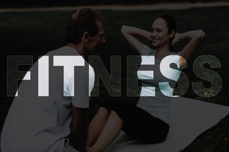 Woman Rocking Press on Nature. Girl Sit on Rug for Yoga. Man Hold Female Legs. Young Fitness Woman. Yoga in Park. Girl in Fitness Training. Person Leads Healthy Lifestyle. Female Smiles. 写真素材