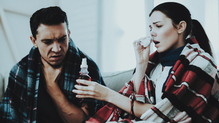 Sick Couple Sitting on Sofa in Checkered Blankets. Man at Home. Sick Young Woman. White Sofa in Room. Unhappy Guy. Disease Concept. Healthcare and Healthy Lifestyle Concept. Using Nasal Spray.
