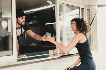 Girl in Black Dress Buying Snacks in Food Truck. Promenade in Town. Summer Day. Girl in Black Dress. Street Food Concept. Cup of Coffee. Buying Food Outdoor. Food in Town. Selling Snacks.