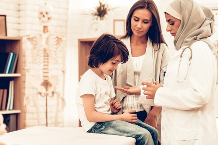 Arabic Doctor Give Medicine to Sick Boy Lying Bed. Confident Muslim Female Doctor Giving Glass of Medicine. Child at the Pediatrician. Hospital Concept. Healthy Concept. Child Patient Visiting Doctor. 版權商用圖片