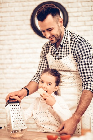 Cook Food at Home. Happy Family. Father's Day. Girl and Man Cook Food. Man and Child at Table. Spend Time Together. Grate Cheese. Grater in Hand. Tomatoes and Cucumber. Kitchen Process. Bite Cheese.
