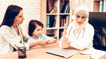 Arabic Doctor Refusing Bribes or Kickbacks, Money. Mom Giving to Doctor Money. Confident Muslim Female Doctor. Child at the Pediatrician. Hospital Concept. Healthy Concept. Child Patient Visiting Doctor. Foto de archivo