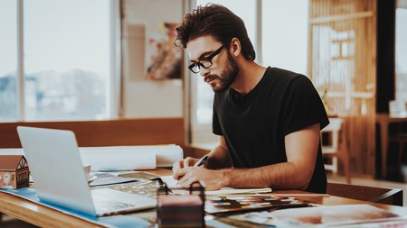 Graphic Designer Concentrated on Work Project. Portrait of Young Bearded Illustrator Sitting at Workplace Looking at Laptop Screen Writting in Notepad Indoors. Creative Job Concept Stock Photo