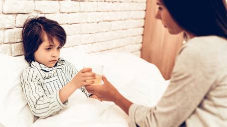 Mother Giving Medicine to Sick Son Lying Bed. Caring Mom Giving Sick Boy Pills. Worried Mother Giving Glass of Water to Ill Kid. Hospital Concept. Healthy Concept. Parent Concept. Stock Photo