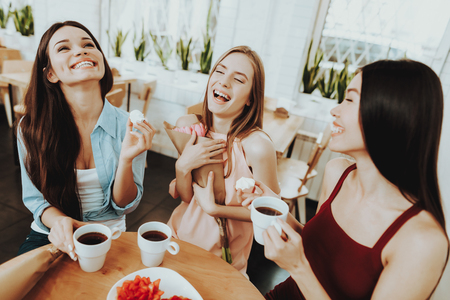 Happy Woman Drinking Tea with Biscuit. Springtime with Tea and Biscuit. Celebrate 8 March with Family and Friends. Tenderness and Happy in this Day for all Women. Beautiful Woman with Young Girl. Banco de Imagens