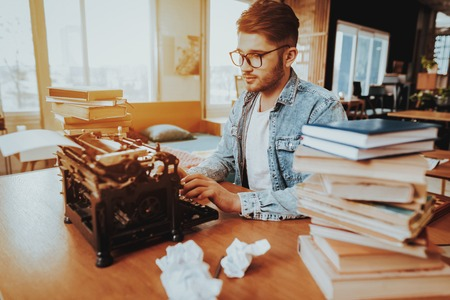 Text Writer Working on Typewriter Sits at Desk. Pensive Handsome Hardworking Freelance Screenwriter Scenarist Sits Near Stacks of Books Writing Play. Antique Retro Style of Work