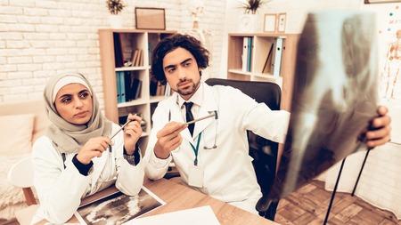 Arabic Doctors Having Consultation, X-Ray Film. Muslim Doctors Having Consultation in Office. Arabic Doctors Holding X-Ray, Medical Consultation. Hospital Concept. Healthy Concept. Healthcare And Medicine.