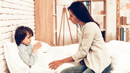 Matka daje lekarstwo choremu synowi w łóżku. Opiekuńcza mama daje choremu chłopcu pigułki. Zmartwiona matka daje choremu dziecku szklankę wody. Koncepcja szpitala. Zdrowa koncepcja. Koncepcja nadrzędna. Zdjęcie Seryjne