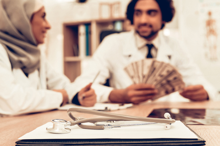 Arabic Doctors Counting Money After Work, Payday. Muslim Doctors Counting Dollars in Office. Arabic Doctors Holding Money, Medical Consultation. Hospital Concept. Healthy Concept. Healthcare And Medicine.