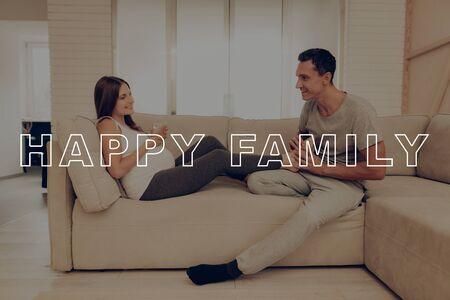 Glückliche junge Familie. Mann knetet Frau-Füße. Schwangere Frau liegt auf hellem Sofa.