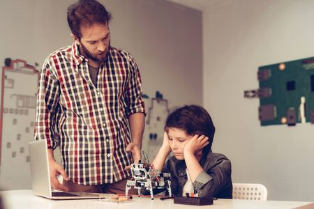 Bearded Father Help Upset Son with Robot at Home. Young Boy in Shirt. Using Laptop. Modern Hobby Concept. Modern Technology. Robot Engineering Concept. Bearded Young Man. Innovation for Fun.