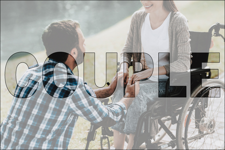 Couple in Love. Man and Disabled Girl in Park. Happy Couple Sitting in Park and holding Hands Together. Handsome Man and Beautiful Girl in Wheelchair on Romantic Date. Love and Relationship Concept