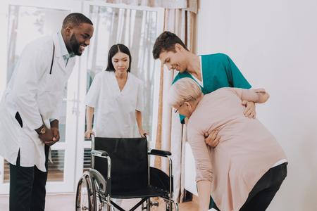 L'infirmière aide la femme à sortir du lit. Maison de repos. Une femme âgée se met en fauteuil roulant. La femme se sent faible. Docteur en Clinique. Le docteur aide le patient à se lever. Patient en fauteuil roulant. Pensionné en réadaptation. Banque d'images