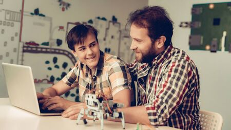Bearded Father Help Son to Program Robot at Home. Young Boy in Shirt. Using Laptop. Modern Hobby Concept. Modern Technology. Robot Engineering Concept. Bearded Young Man. Innovation for Fun. Imagens