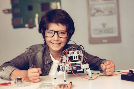 Boy Sitting at Desk and Constructing Robot at Home. Young Boy in Shirt. Indoor Joy. Modern Hobby Concept. Modern Technology. Robot Engineering Concept. Teenager with Robor. Innovation for Fun.