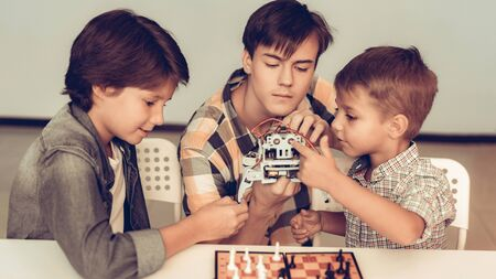 Teenager Demonstrating Robot to Two Sitting Boys. Young Boy in Shirt. Indoor Joy. Modern Hobby Concept. Modern Technology. Robot Engineering Concept.
