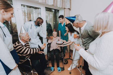Group Young and Old People Congratulate Woman. Birthday in Nursing Home. Elderly Female Very Surprised. Woman Very Happy. Guests Hold Glasses of Drinks. Nurse Hold Cake. Birthday Party Celebration. Standard-Bild