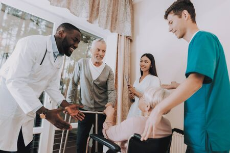 Male Rehabilitation. Doctor Tells about Cure. Doctor in Nursing Home. Patient with Walker. Nursing Home. Man with Crutches. Patient on a Wheelchair. Sitting Elderly Woman. Patient Smiling.