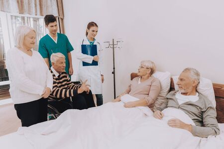 Nurse with Papers. Guests Visit Elderly Couple. Man Dripping. Elderly People Lay in Bed. Nursing Home. Man Sitting in Wheelchair. Smling Group of Patient. Pensioners on Rehabilitation.
