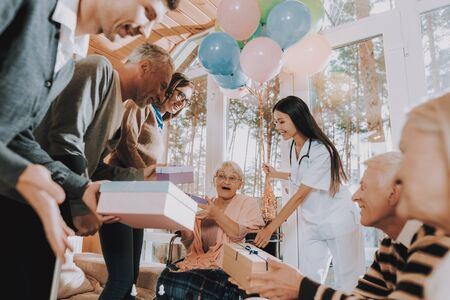 Nursing Home. Madly Happy Retiree in Wheelchair. Guests Give Gifts to Elderly Woman. Birthday Party Celebration. Very Happy Young and Old People. Madly Happy Retiree. Old Woman Very Surprised.