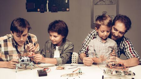 Bearded Father and Sons Constructing Robot at Home. Young Boy in Shirt. Indoor Joy. Modern Hobby Concept. Modern Technology. Standard-Bild