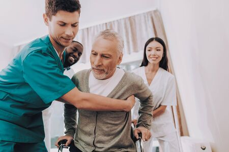Doctor Helps Patient Get Up. Patient in Wheelchair. Male Get Out of Bed. Nurse Helps. Doctor in Clinic. Elderly Man Sit in Wheelchair. Man Feels Weak. Nursing Home. Elderly Man in Rehabilitation.