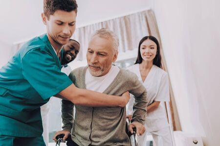 Le docteur aide le patient à se lever. Patient en fauteuil roulant. Homme sortir du lit. Infirmière aide. Docteur en Clinique. Un homme âgé s'assoit en fauteuil roulant. L'homme se sent faible. Maison de repos. Homme âgé en réadaptation. Banque d'images