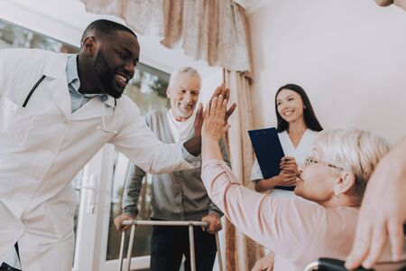 Doctor High Five Patient. Male Rehabilitation. Doctor in Nursing Home. Patient with Walker. Nursing Home. Man with Crutches. Patient on a Wheelchair. Sitting Elderly Woman. Patient Smiling.