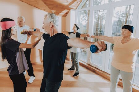 Elderly People Engaged. Old Men with Equipment. Patient Wearing Sport Uniform. Young Instructor Show Exerscises. Active Retiree Nursing Home. Therapeutic Gymnastics. Old People Healthcare Lifestyle.