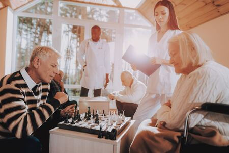 Senior Man and Woman Play Chess. Nursing Home. Sitting Old Woman. Doctor and Nurse Stand Nearby. Elderly Male Rehabilitation. Patient on a Wheelchair. Young and Old People in Nursing Home. Standard-Bild