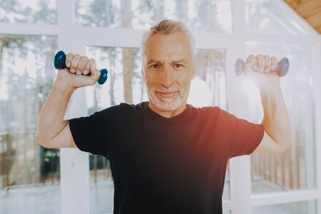 Active Retiree Wearing Sport Uniform. Smiling Patient Do Exercises. Elderly Hold Dumbbells. Therapeutic Gymnastics in Nursing Home. Man Looks Confident in Abilities.