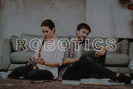 Young Couple Sit on Floor. Work Together. Family Living Room. Girl Help Guy Create Robotics. Happy Family. Guy Work with Mechanical Robot. Man Fall in Work. Guy Designing Robot. Man Work at Home.